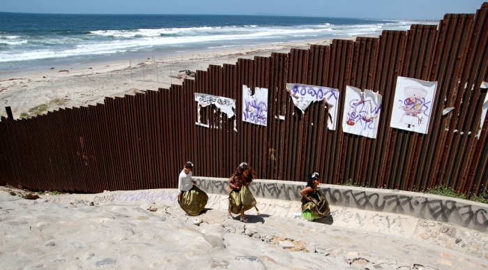 Tres niñas en vestido de quinceañeras juegan en Tijuana al lado del muro de la frontera México-USA. Fotografía: Romel Jacinto. Flickr. CC.